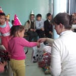 Maggie passing out birthday presents to her primary class kids
